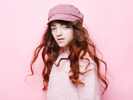 Image of happy teen girl standing isolated on pink background, in pink hat and sweater. Lifestyle and fashion concept.