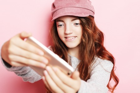 cheerful little girl with curly hair l taking a selfie isolated over pink background