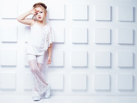 Cute little blond girl wearing white casual clothes on a white background. Fashion style.