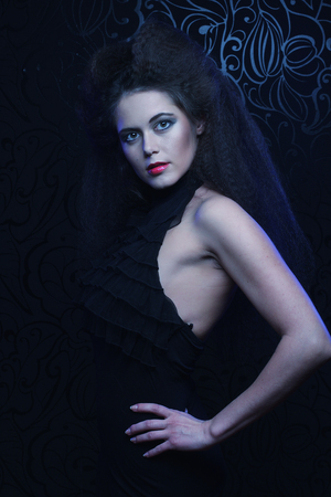 Young brunette woman with high hair and bright make up, gothic style