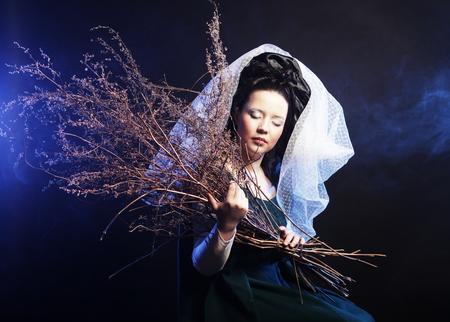 Mujer en traje medieval con montón de palos en humo