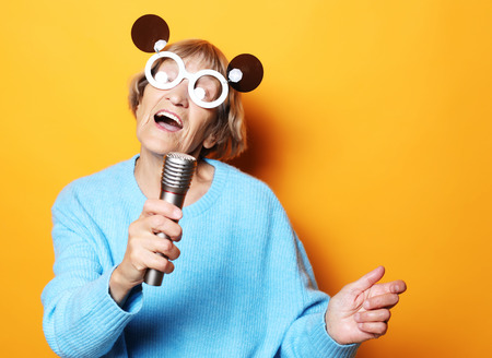 happy old woman with big eyeglasses holding a microphone and singing isolated on yellow background Imagens