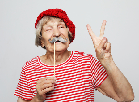 lifestyle, people and party concept: funny grandmother wearing red clothes holding falce glasses