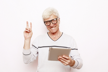 lifestyle, tehnology and people concept: Happy senior man using digital tablet.
