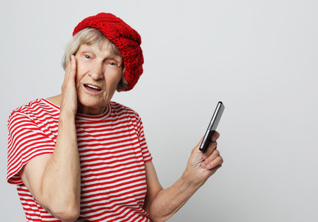 old granny looks at her smart phone and is surprised Archivio Fotografico
