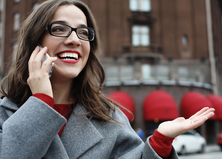 Outdoor portrait of surprised young woman with eyeglasses wearing grey coat and holding smartphone.