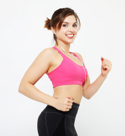 portrait of a smiling fitness woman in headphones working out isolated over white background