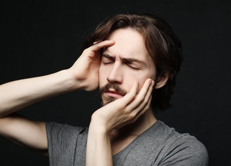 unhappy man touching his forehead over black background