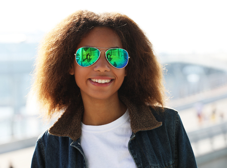 woman wearing sunglasses with perfect teeth and dark clean skin having rest outdoors, smiling after received good positive news.