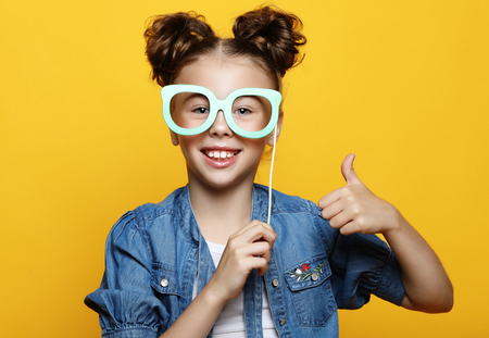party, childhood and people concept: little girl with a paper accessories over yellow background. Standard-Bild