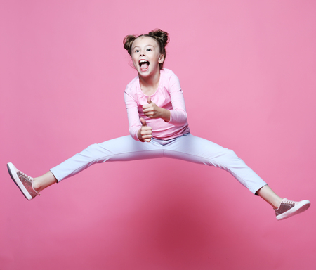 funny child girl dressed casual jumping on pink  background 写真素材