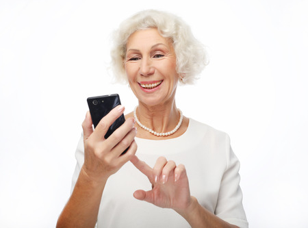 Smiley senior woman is holding a new smartphone in her hand. Stock Photo