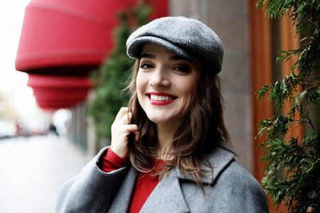 young stylish pretty woman wearing red dress, grey coat and hat