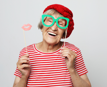 funny grandmother wearing red clothes holding falce glasses and ready for party Stock Photo