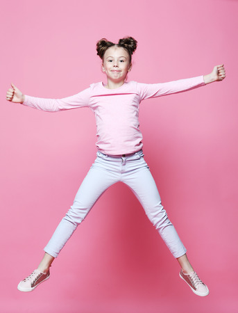 funny child girl dressed casual jumping on pink  background Stock fotó