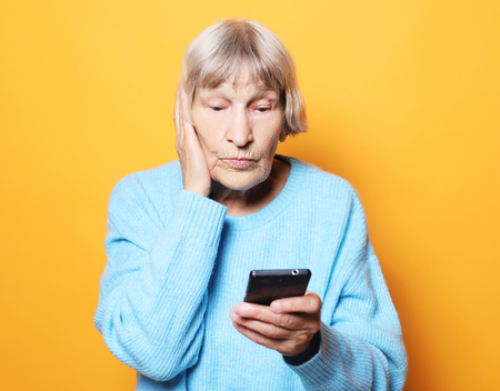 old granny looks at her smart phone and is surprised