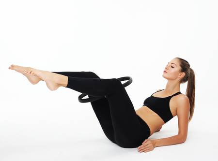 Young sporty woman with perfect body having a training with pilates ring over white background
