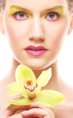 young woman with bright make up holding orchid