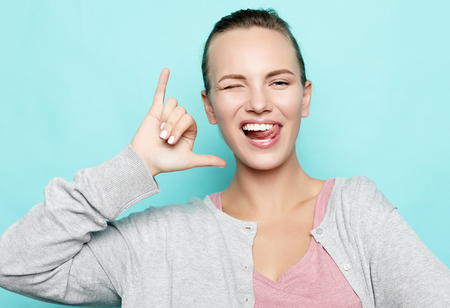 funny girl showing her tongue while posing against studio background. Emotional positive young female making faces Imagens - 116499175