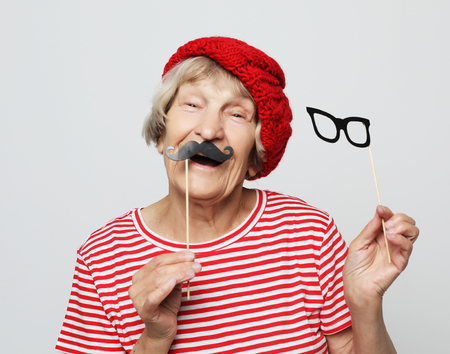 Lifestyle  and people concept: funny grandmother with fake mustache and glasses, laughs and prepares for  party