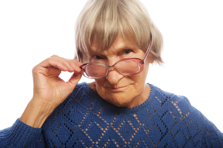 Old senior lady looking through her eyeglasses