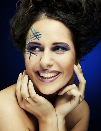 young female face with bright fashion multicolored make-up