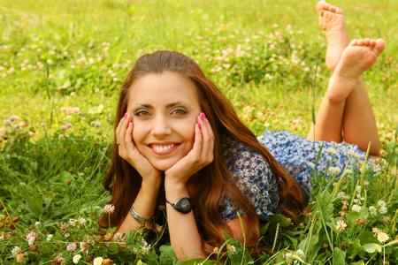young beautiful girl lays on a grass Фото со стока