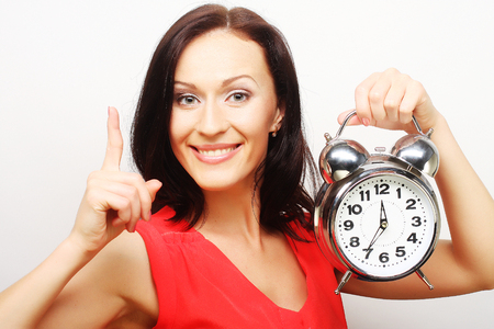 Young happy woman with alarmclock