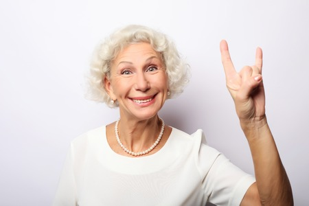 Elderly happy woman giving a thumb up and looking at the camera