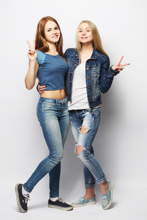Two young girl friends standing together and having fun.