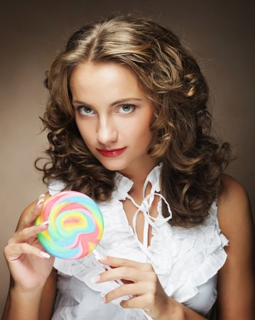 Beauty curly girl portrait holding colorful lollipop.