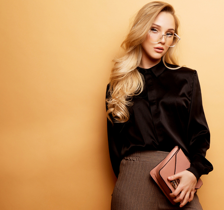 young beautiful woman in a brown blouse and pants holds a handbag and posing on a beige background. 版權商用圖片