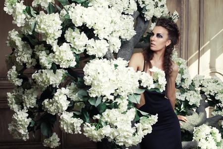 beautiful queen in black dress posing near tree Фото со стока