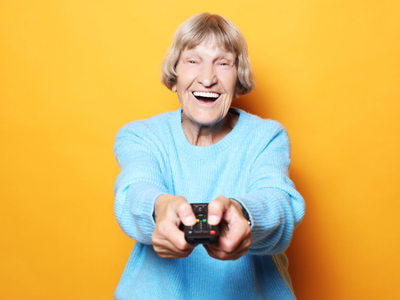 lifestyle, emotion  and people concept: funny grandma is holding a TV remote over yellow background
