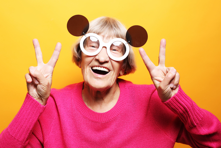Elderly happy woman showing victory sign and looking at the camera