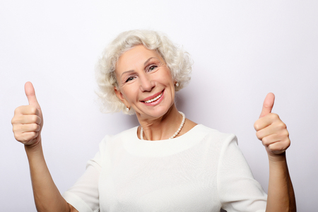 Elderly woman giving a thumb up and looking at the camera Imagens