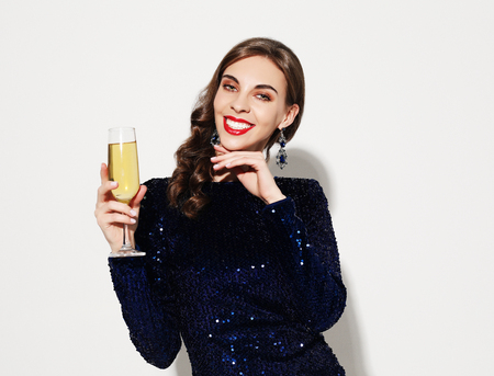 beautiful girl in a cocktail dress with evening make-up and curls holding a glass of champagne