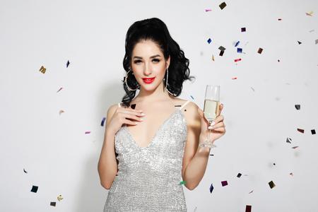 Belle fille portant une robe de soirée debout sous la pluie de confettis Banque d'images