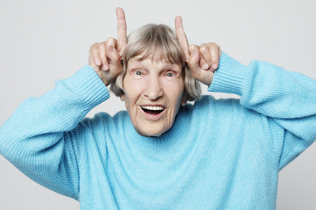 charming grandmother makes horns from fingers