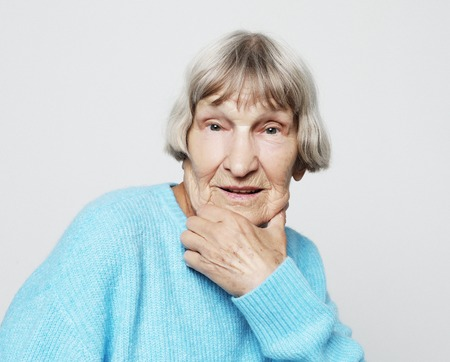 Portrait of handsome grandmother in blue sweater. Dreaming, wondering concept