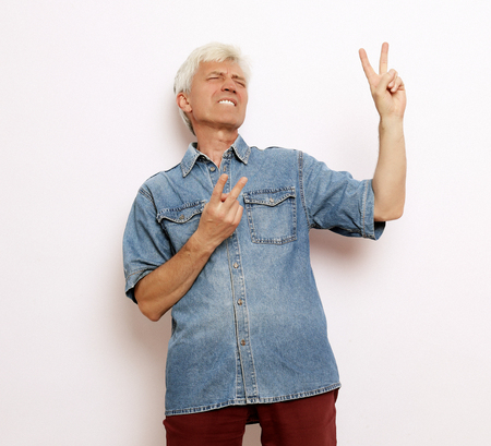 lifestyle, emotion and people concept: Handsome mature man in casual wear is showing victory sign