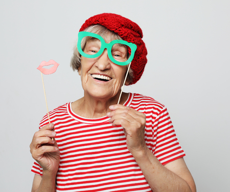 lifestyle, people and party concept: funny grandmother wearing red clothes  ready for party