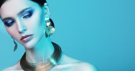 色の光の優雅な宝石を身に着けている美しいファッションモデル
