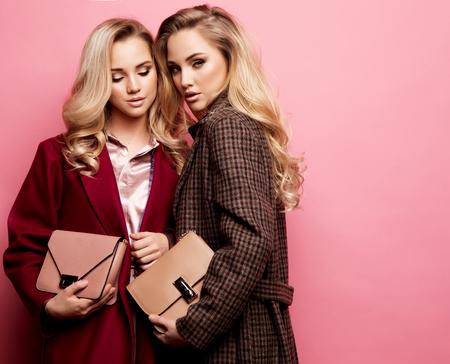 Zwei süße junge Frauen posieren in schönen Kleidern, Mantel, Handtasche. Schwestern, Zwillinge. Frühlingsmodefoto.