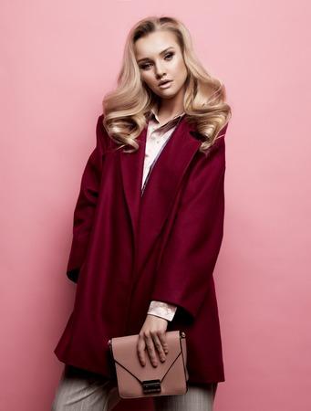 Concepto de moda, personas y estilo de vida: hermosa mujer de pelo largo y rizado rubio llevar abrigo de cachemir y bolso de explotación.