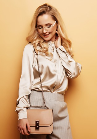 Stylish blond woman in blouse and pants posing on beige background.