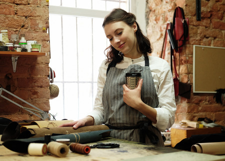 Young woman works in a bag making studio, cuts out details Foto de archivo