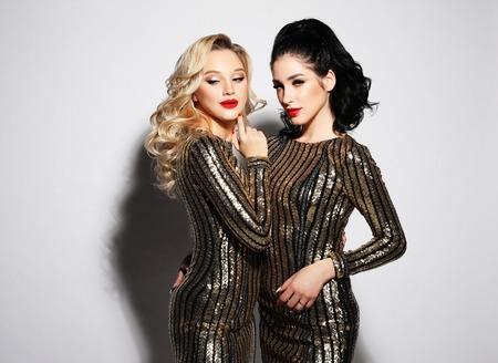 Lifestyle and people concept - Two glamour women in luxury glitter sequins dress drinking champagne and having fun