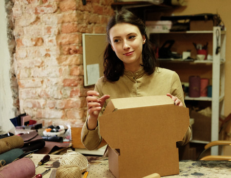 Woman folds packing box in sewing workshop Imagens