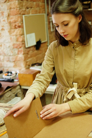 Woman folds packing box in sewing workshop Stok Fotoğraf